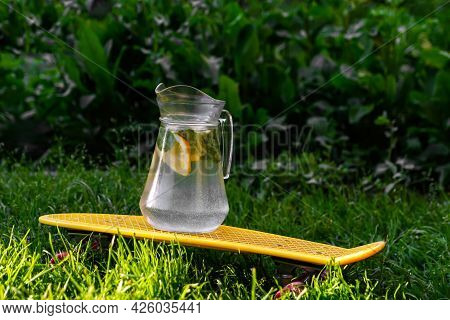 Defocus Glass Jug Of Lemonade With Strawberry, Slice Lemon And Leaves Of Mint On Yellow Penny Board,