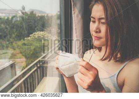Portrait Of Asian Woman Holding A Dust Mask Before Wearing It For Prevent Pm2.5 Bad Air Pollution. A