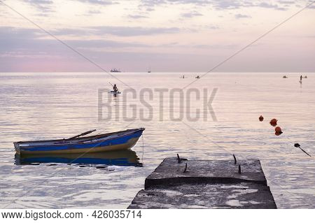 Dawn At Sea Boat In Water And A Girl On A Board With An Oar. Relaxation, Yoga And Water Recreation I