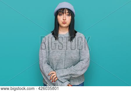 Young hispanic woman wearing cute wool cap puffing cheeks with funny face. mouth inflated with air, crazy expression.
