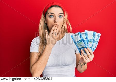 Young caucasian woman holding 1000 hungarian forint banknotes covering mouth with hand, shocked and afraid for mistake. surprised expression