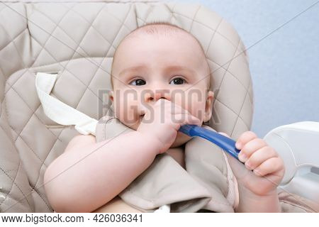 Feeding The Baby. Mom Feeds The Child Vegetable Puree With A Spoon. The Crying Baby Sits On The High