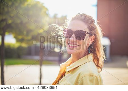 Young Positive Woman Looking Back With Toothy Smile At Outdoors In Park