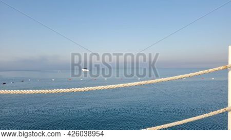 Minimal Seascape In Shades Of Pastel Colors With Morning Sunlight. Nautical Ropes On Foreground And