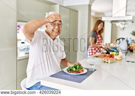 Middle age hispanic couple eating healthy meal at home stressed and frustrated with hand on head, surprised and angry face
