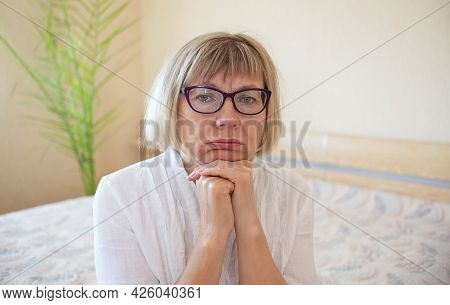 Sad Senior Woman With Glasses Is Sad In Her Home In Bedroom. Loneliness Concept