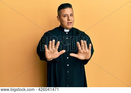 Young latin priest man standing over yellow background moving away hands palms showing refusal and denial with afraid and disgusting expression. stop and forbidden.