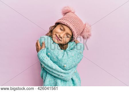 Little beautiful girl wearing wool sweater and cute winter hat hugging oneself happy and positive, smiling confident. self love and self care