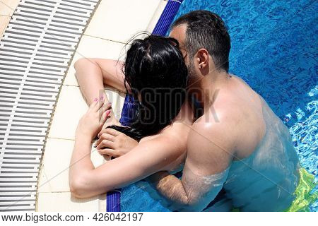 Passionate Couple Hugs And Kisses In The Pool Water. Romantic Vacation Or Honeymoon, Passion And Lov