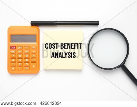 Calculator, Magnifying Glass, Pen And Notepad Wirtten Cost-benefit Analysis. Cost-benefit Analysis I