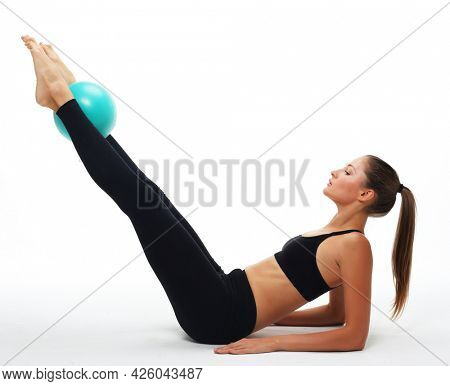 Young fit adult woman doing yoga exercise workout with gymnastics ball.
