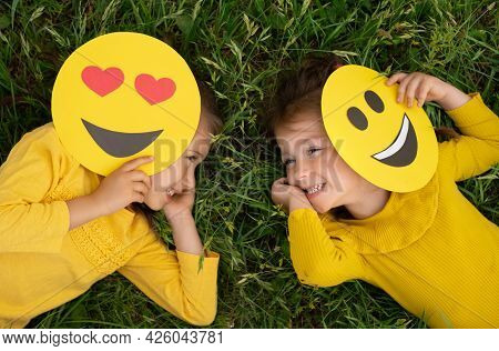 Two Funny Little Girls Are Lying On The Lawn Covering Part Of Their Faces With Emoticons And Laughin
