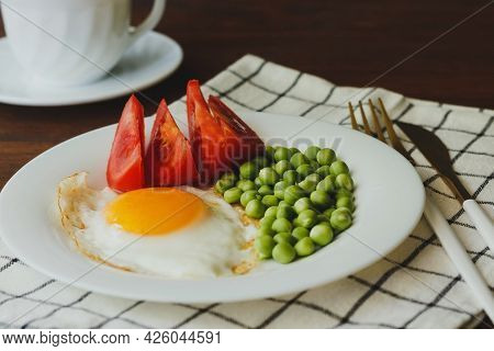 Plate Of Fried Eggs With Vegetables On Wooden Table.