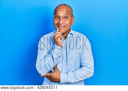 Middle age latin man wearing casual clothes and glasses looking confident at the camera with smile with crossed arms and hand raised on chin. thinking positive.