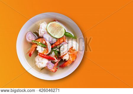 Tom Yum Goong In A White Cup On An Orange Background. Thai Food That Has Been Accepted All Over The