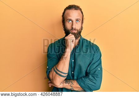 Handsome man with beard and long hair wearing casual clothes thinking concentrated about doubt with finger on chin and looking up wondering