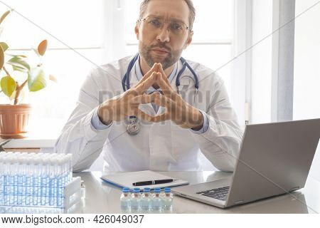 A Doctor With A Stethoscope During Online Consultation Looks Closely At The Camera, Listening To You