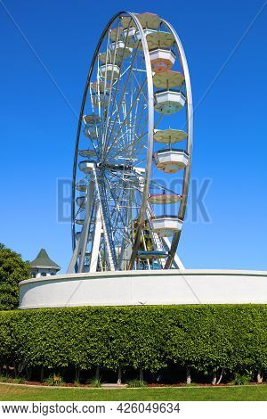 July 6, 2021 In Long Beach, Ca:  Vintage Wooden Carousel Besides Manicured Gardens Taken At The Pike