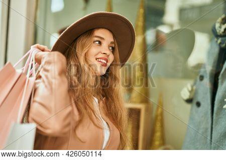 Young blonde girl shopping looking showcase shop.