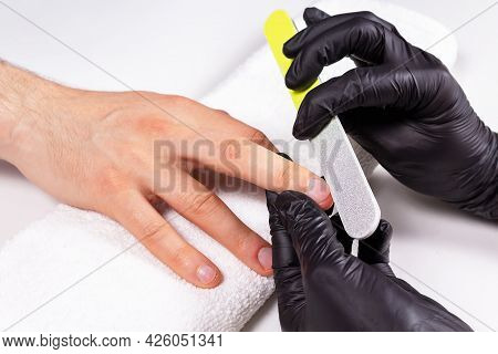 Manicurist In Black Gloves Doing Man's Manicure. Young Businessman Doing Manicure. Take Care Of Your