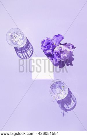 Two Glasse With Water And Card Note With Iris Flower On Pastel Lilac Background. Summer Refreshment