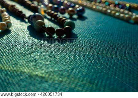 Heap Of Colored Bright Jewelry Beads On A Blue Background. Different Gems Beads Necklace. Jewel Neck