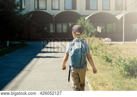 The Cute Girl, Elementary School Student, Walking To School With Bag Behind Back And Book. Students