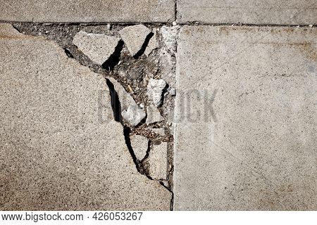 Texture of cracked sidewalk concrete with cigarrete in crack