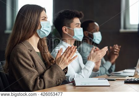 Colleagues In Masks Having Meeting In Boardroom, Clapping Hands