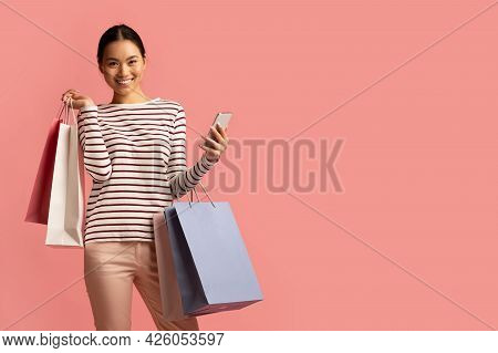 Online Shopping. Cheerful Asian Female Holding Smartphone And Bright Paper Shopper Bags
