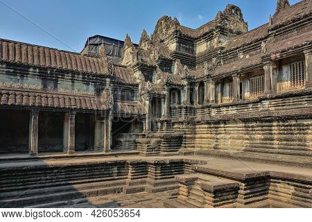 Fragment Of The Ancient Temple Of Cambodia Against The Blue Sky. Weathered Stone Terraces With Colum