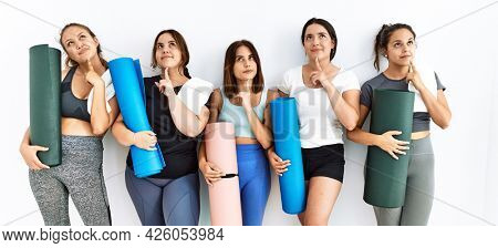 Group of women holding yoga mat standing over isolated background thinking concentrated about doubt with finger on chin and looking up wondering