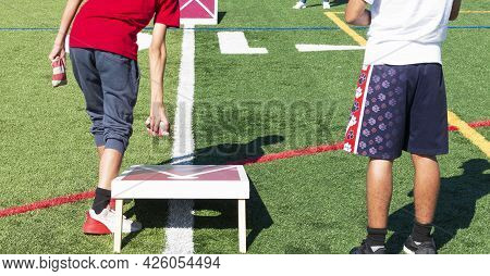 Rear View Of Two Boys Playing Cornhole Bean Bag Toss Game On A Turf Field.