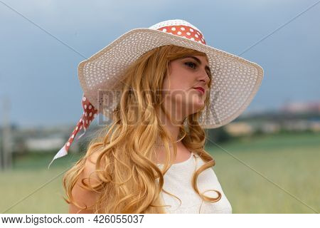 Girl In A White Dress And Hat On A Field Background.