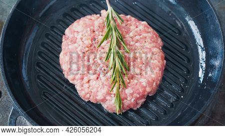 High Angle View Of Mince Patty With Salt And Rosemary Branch On Hot Pan