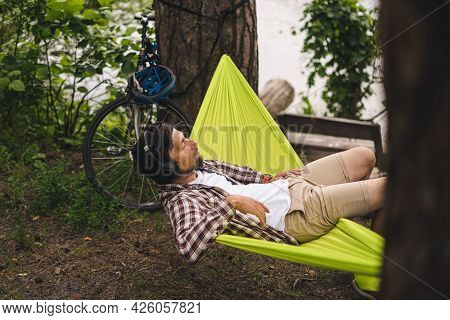 Young Caucasian Man Resting In Hammock, Listening To Music On Headphones And Using Smartphone Afterw