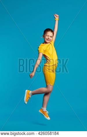 Happy Little Kid In Yellow Sportswear Outfit Smiling, Blinking Her Eyes And Raising Hand While Leapi