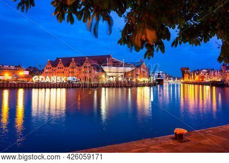 Beautiful scenery of Gdansk city at dusk over the Motlawa river with illuminated Gdansk inscription. Poland