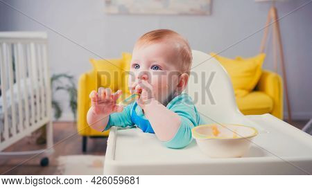 Infant Boy With Blue Eyes Sitting In Feeding Chair And Sucking Spoon Near Bowl With Baby Food