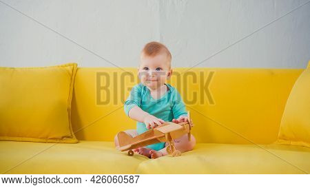 Happy Infant Boy Sitting On Sofa And Playing With Wooden Biplane