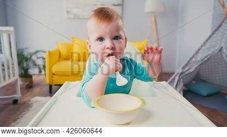 Baby Boy Sitting In Feeding Chair And Sucking Spoon Near Bowl