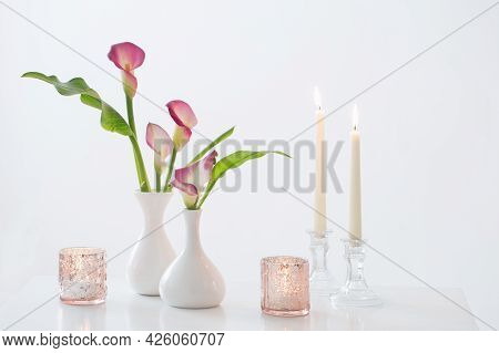Pink Calla Lily In Vase  And Burning Candles On White Background