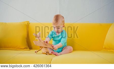 Baby Boy Sitting On Sofa And Playing With Wooden Biplane