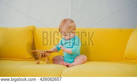 Infant Boy Sitting On Sofa And Playing With Wooden Biplane