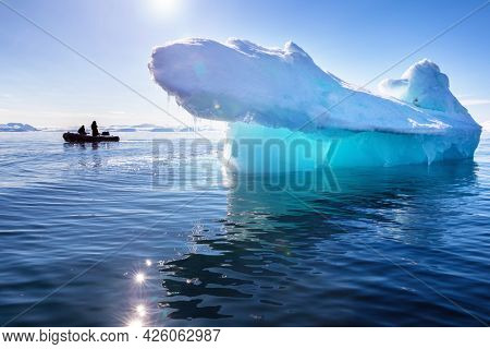 Blue iceberg in Nordfjorden, Svalbard. Sunlight is shining through, showing the vibrant blue and turquoise tones. A small expedition boat can be seen silhouetted behind with unidentifiable tourists.