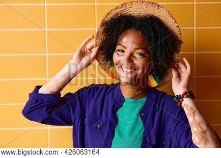 Portrait Of Smiling Woman With Vitiligo In A Straw Hat Dressed In Stylish Clothes Near Orange Buildi