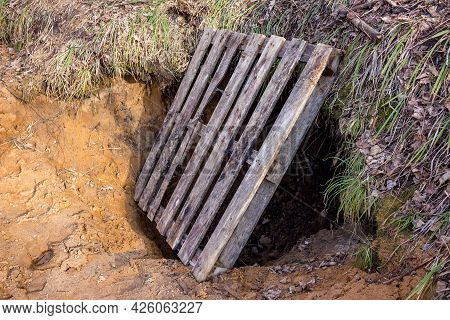 A Dugout Dug In The Sand Covered With A Wooden Pallet, Digging Tunnels In The Sand On The Slope Of A