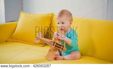 Infant Boy Sitting On Couch And Playing With Wooden Biplane