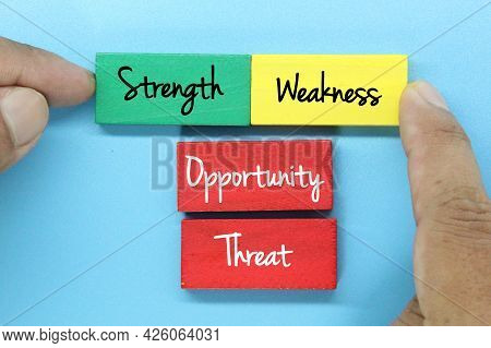 Colored Wooden Blocks With The Words Threat Opportunity Weakness Strength