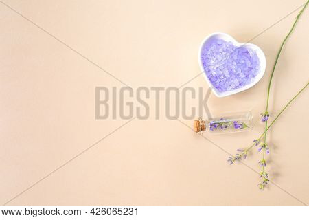 Lavender Sea Salt In A Heart-shaped Plate, Bottle, And Sprigs Of Lavender On A Beige Background With
